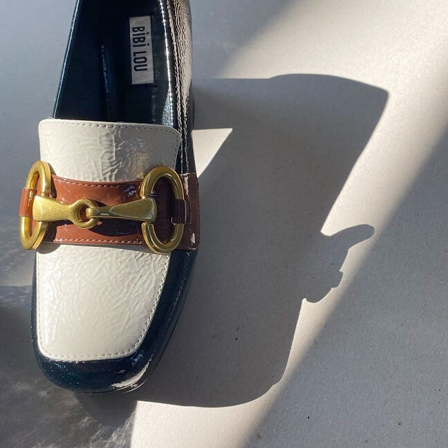 Close-up donkerblauw wit bruine loafers met ketting details